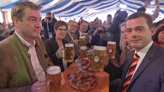 CDU-Parteichefin Annegret Kramp-Karrenbauer, CSU-Chef Markus Söder und CDU-Spitzenkandidat für die Landtagswahl 2019 Mike Mohring sitzen gemeinsam mit anderen Menschen auf Bierbänken in einem Festzelt und halten je einen Maßkrug Bier in der Hand.