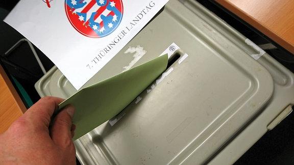 Ein Mann steckt einen Wahlzettel in die Wahlurne.
