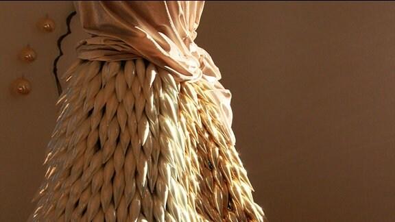 Gläserner Christbaumschmuck aus Lauscha an einem Kleid