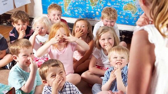 Kinder machen Lernspiele mit der Erzieherin.