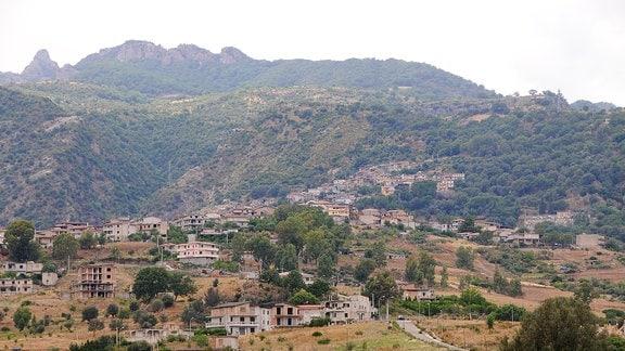 An einem Berghang stehen mehrere Wohnhäuser über das Gelände verteilt.