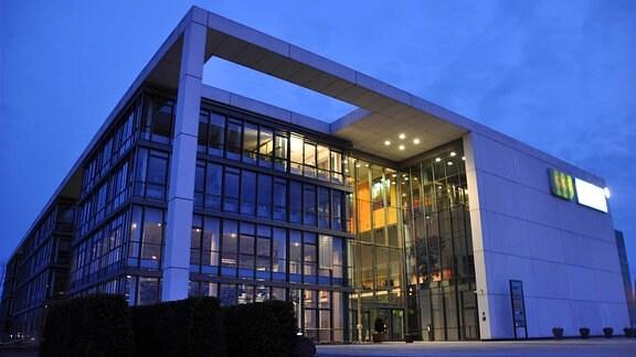 Blick auf den Eingang und das erleuchtete Foyer des MDR-Landesfunkhauses Thüringen in Erfurt.