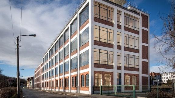 Ein vierstöckiges Industriegebäude mit großen Fenstern
