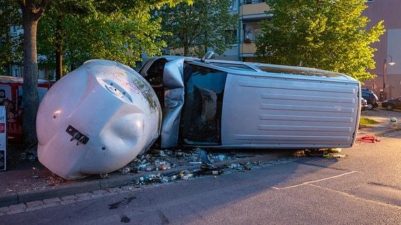 Ein Kleintransporter liegt auf der Seite, nachdem er bei einem Unfall in Kranichfeld gegen Glascontainer gefahren war