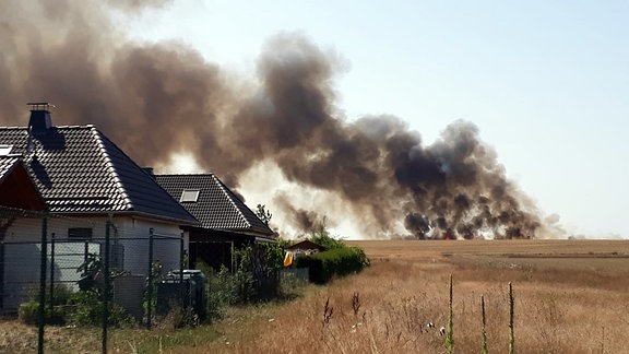 Häuser stehen an einem Feld, dahinter eine schwarze Rauchwolke