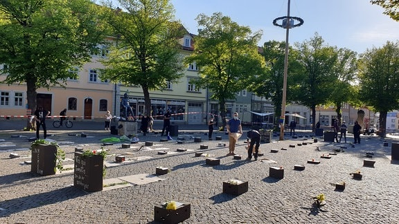 Auf dem Marktplatz in Arnstadt liegen Pappkartons, die wie Grabsteine aussehen sollen. Mit der Aktion soll der Toten der Corona-Pandemie gedacht werden