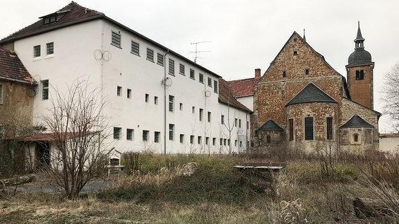 Trakt der ehemaligen Jugendstrafanstalt Ichtershausen und Kirche.