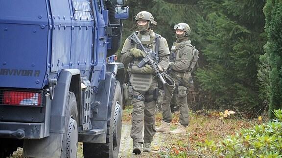SEK-Polizisten gehen neben einem Wasserwerfer