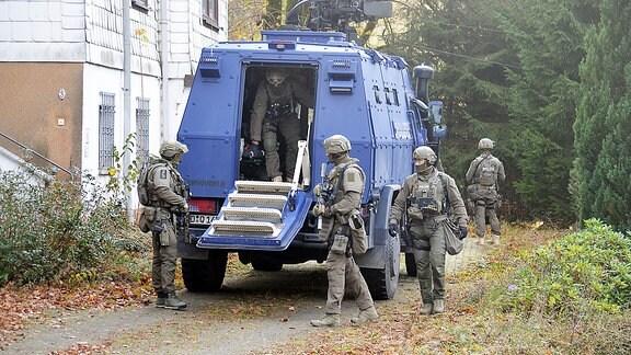 Vier SEK-Polizisten vor einem Wasserwerfer
