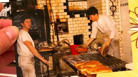 Ein altes Foto zeigt zwei Bäcker in einer Backstube.