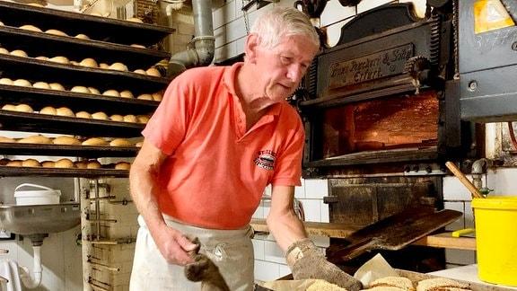 Bäcker Wigbert Weißleder holt Brote aus einem Ofen
