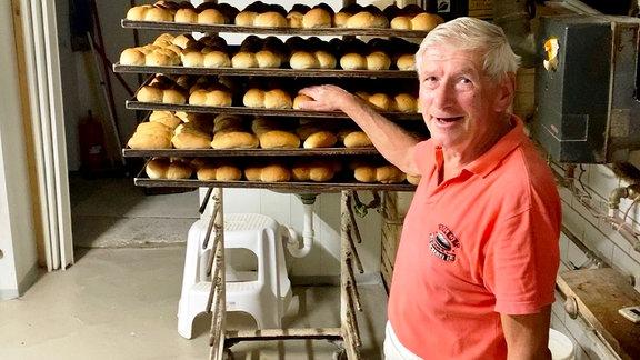 Bäcker Wigbert Weißleder zeigt auf ein Regal mit Brötchen