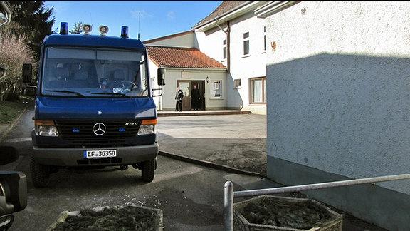 Ein dunkles Einsatzfahrzeug der Polizei steht im Hinterhof eines weiß gestrichenen Gebäudes.