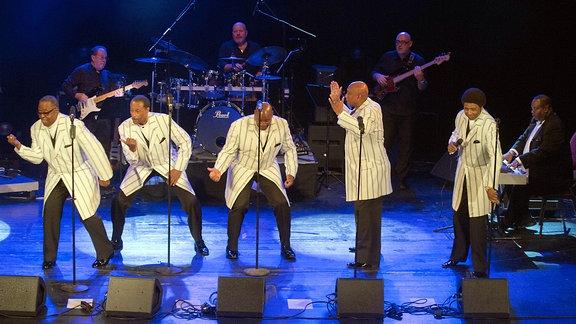 Fünf Sänger in hellen Jackets stehen auf einer Bühne und singen. Im Hintergrund spielen mehrere Musiker