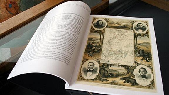 Aufgeklapptes Buch mit historischen Karten.