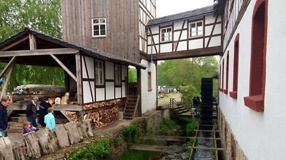 Wasser fließt von einem hölzernen Mühlrad in einer Rinne durch einen Graben neben den Gebäuden der Senfmühle Kleinhettstedt