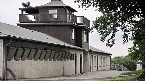 Blick auf das Lagertorgebäude des KZ Buchenwald, im Hintergrund sind Stacheldrahtzäune zu sehen