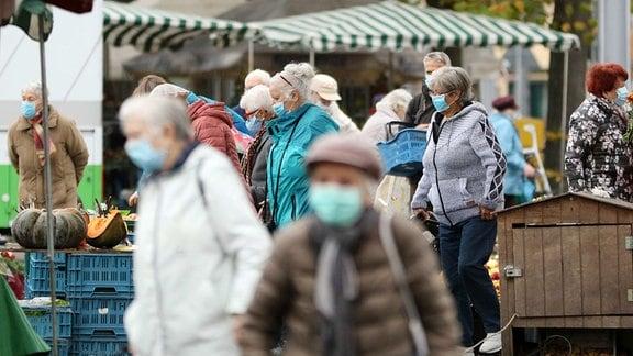 Besucher eines Wochenmarktes auf dem Domplatz in Erfurt tragen Masken.