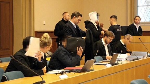 Angeklagte und ihre Anwälte im Prozess um falsche Polizisten in einem Gerichtssaal in Erfurt