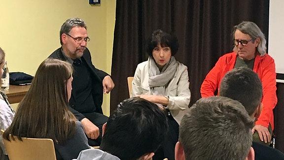 Eine Frau mit schwarzen, halblangen Haaren und einer weißen Jacke sitzt zwischen zwei Männern auf einem Stuhl, vor ihr sitzen Jugendliche in einem Publikum