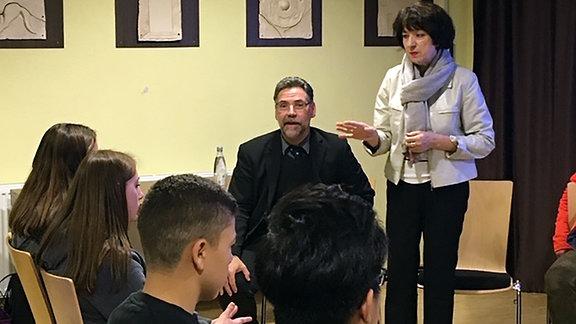 Eine Frau mit schwarzen, halblangen Haaren und einer weißen Jacke steht neben einem Mann und redet, vor ihr sitzen Jugendliche in einem Publikum