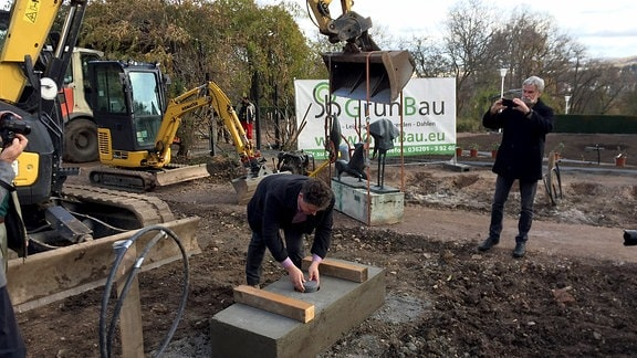 Egapark-Betriebsleiter Chris Lange versenkt eine Zeitkapsel bei Bauarbeiten im Rosengarten