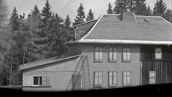 Ein Haus mit verschlossenen Fensterläden im Wald.