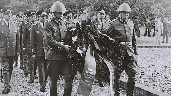 Männer in Uniformen tragen einen Gedenkkranz.