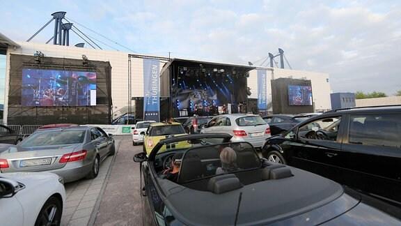 Parkende Autos vor der Bühne.
