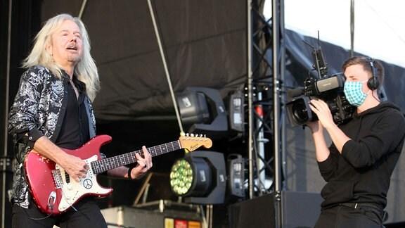 Kameramann mit Mundschutz filmt Gitarrist.