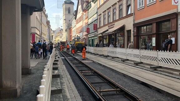Männer bauen auf einer Straße Gleise ein.