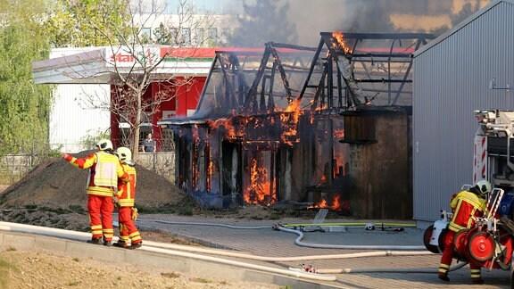 Feuerwehrleute vor einem brennenden Gebäude
