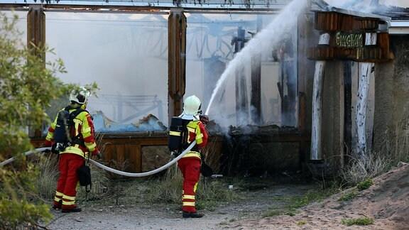 Zwei Feuerwehrmänner spritzen Wasser aus einem Schlauch in ein brennendes Gebäude