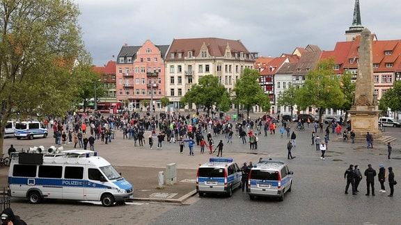 Eine Menschenmenge auf dem Domplatz, davor Polizeiautos.