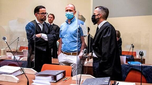 Mark Schmidt (Mitte) steht mit seinen zwei Anwälten hinter Plexiglas im Gericht.