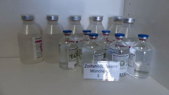 In einem weißen Standregal steht eine Vielzahl von Flaschen mit Kochsalzlösung in der rechten Ecke eines Fachs