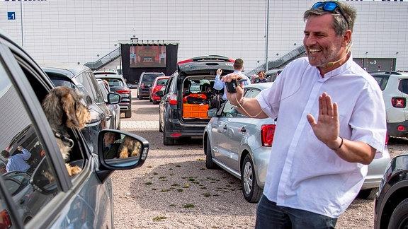 Der Pfarrer der Erfurter Thomasgemeinde, Christoph Knoll, spricht auf dem Messe-Parkplatz mit den Insassen eines Autos.