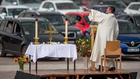 Pfarrer Christoph Knoll von der Erfurter Thomasgemeinde steht neben einem improvisierten Altar auf dem Messe-Parkplatz in Erfurt.