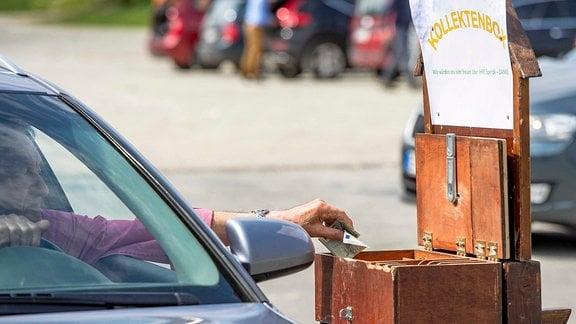 Ein Autofahrer legt auf dem Parkplatz der Messe Erfurt aus dem Autofenster heraus einen Geldschein in eine Kollektebox der Thomasgemeinde Erfurt.