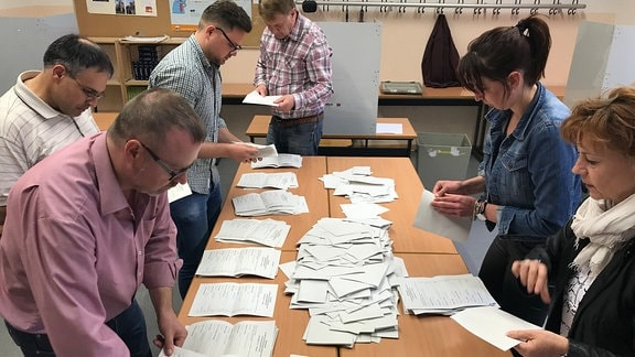 Mehrere Männer und Frauen zählen Stimmzettel während der Kommunalwahl 2018 in Thüringen in einem Raum des Ratsgymnasiums in Erfurt aus