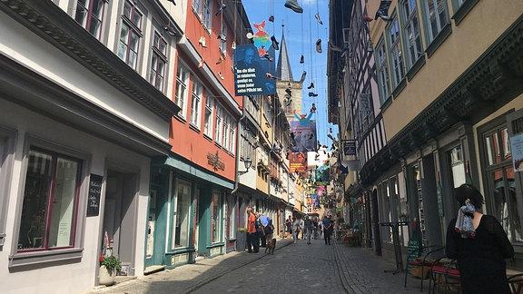 Zwischen zwei Häuserreihen auf der Krämerbrücke in Erfurt hängen Schuhe an langen Leinen.