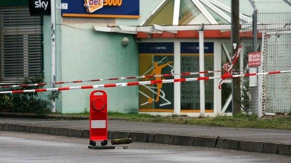 Vor einer Gaststätte in Erfurt ist rotes Absperrband der Polizei aufgespannt.