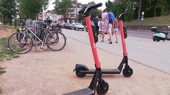 Zwei E-Scooter parkt neben Fahrrädern in Erfurt.