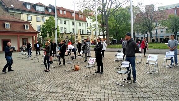 Gastronomen aus Thüringen stehen vor der Staatskanzlei in Erfurt neben leeren Stühlen