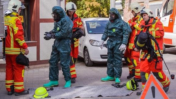 Feuerwehrmänner stehen in einer Gruppe zusammen, einer davon trägt einen besonderen Schutzanzug.