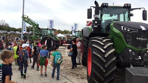 Auf einer Fläche stehen mehrere Traktoren, die sich Kinder anschauen.