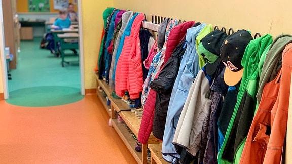 In einer Grundschule hängen Jacken an Haken