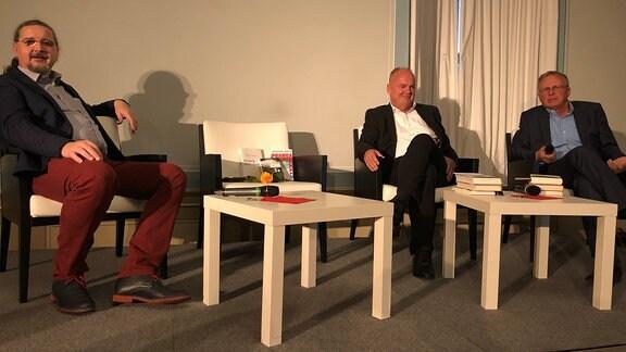 Drei Männer sitzen auf einer Bühne in weißen Sesseln.