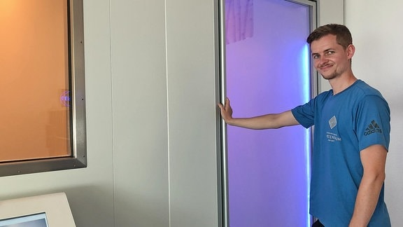 Ein Mann, Sportwissenschaftler Björn Lach, steht vor einem grauen Kasten mit Glastür. Er betreut die Patienten in der Kältekammer.