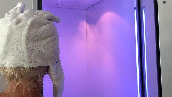 Eine Frau mit einer weißen Pudelmütze guckt in einen lila angestrahlten Raum aus dem weißer Nebel dampft.
